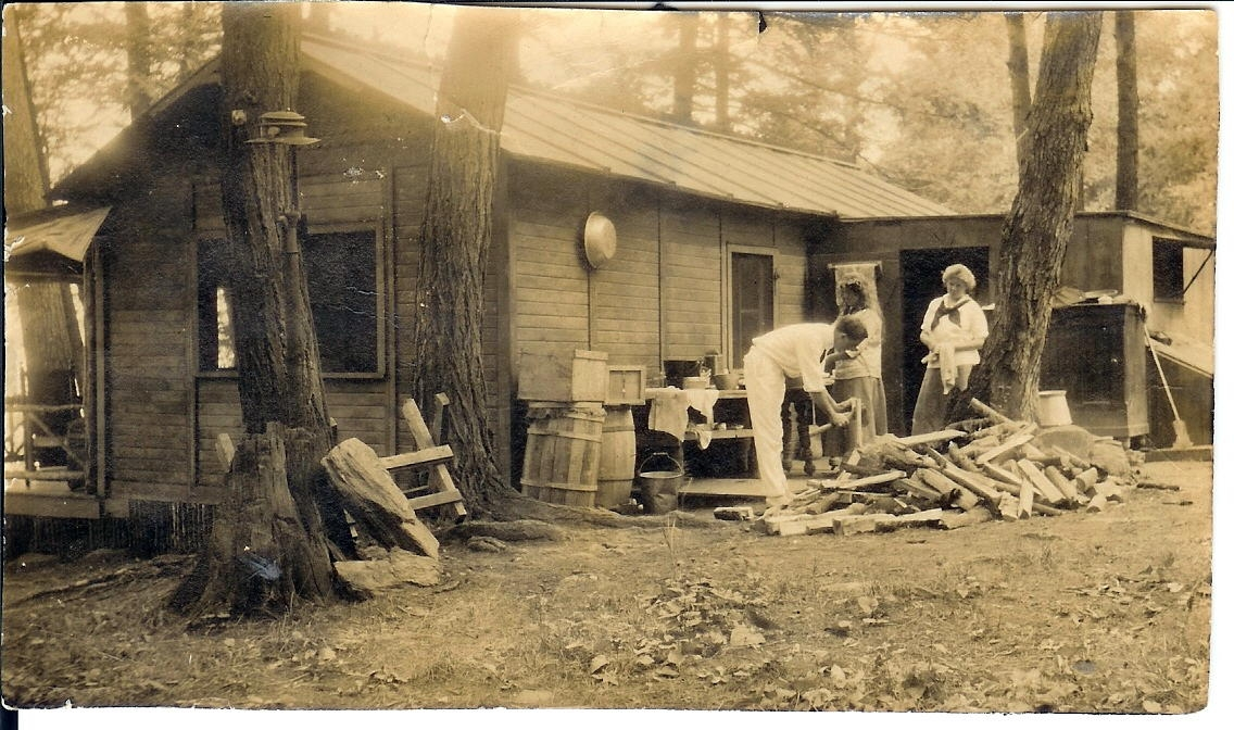 Kelloggs rental cottage, Gus Wessels chopping firewood 1913